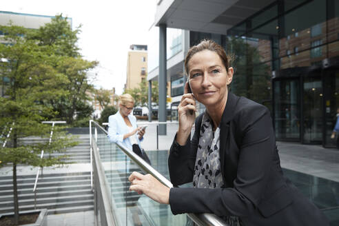 Woman talking on mobile phone while colleague standing in background at city - PMF01401