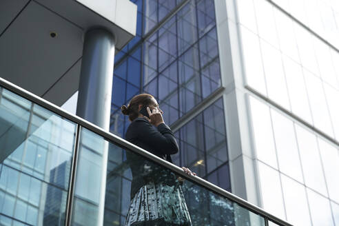 Businesswoman talking on mobile phone while standing by railing against building - PMF01407