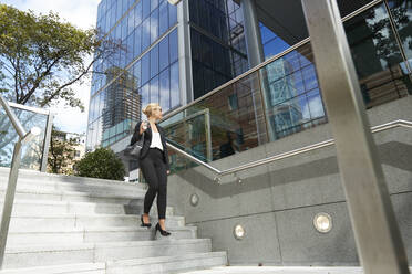 Businesswoman looking away while walking on staircase against building - PMF01410
