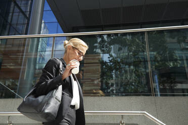 Smiling woman holding coffee cup while walking on staircase against building - PMF01413