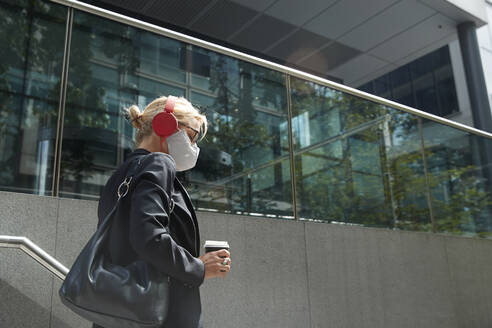 Businesswoman wearing face mask listening music while walking against building - PMF01416