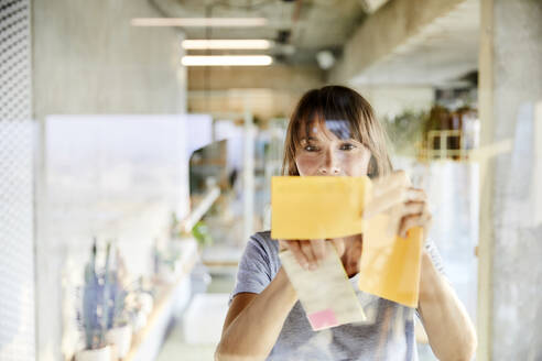 Mature woman sticking sticky notes on glass material - FMKF06510