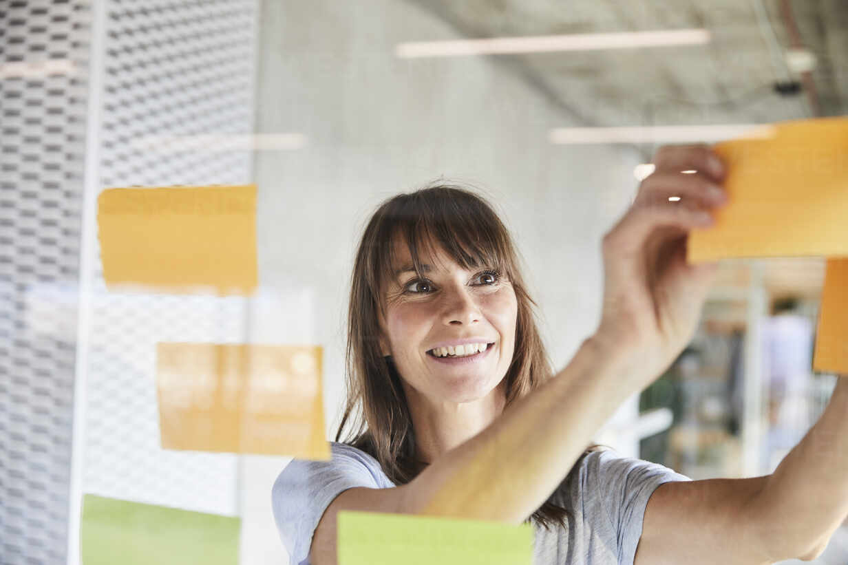 Woman smiling while sticking sticky notes on glass material - FMKF06513 - Jo Kirchherr/Westend61