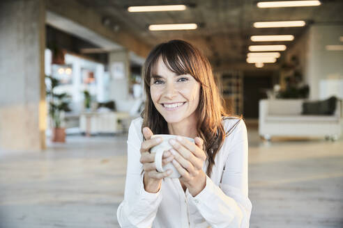 Smiling mature woman holding coffee cup while sitting at home - FMKF06534