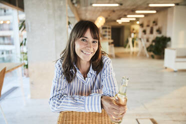Smiling mature woman holding beer bottle while sitting at home - FMKF06540