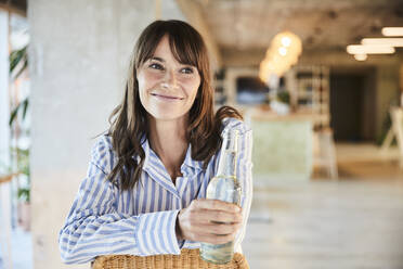 Smiling mature woman looking away while holding beer bottle sitting at home - FMKF06543