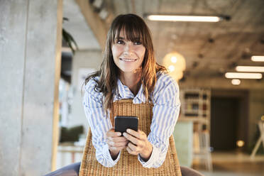 Mature woman smiling while using smart phone sitting at home - FMKF06546