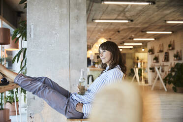 Contemplating mature woman sitting with beer bottle on chair at home - FMKF06552