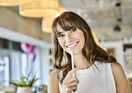 Smiling woman holding digitized pen while standing at home - FMKF06587