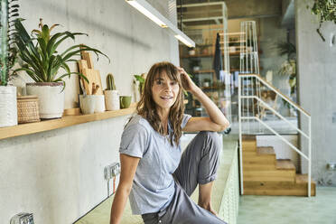 Woman with hand in hair by potted plant rack at home - FMKF06620