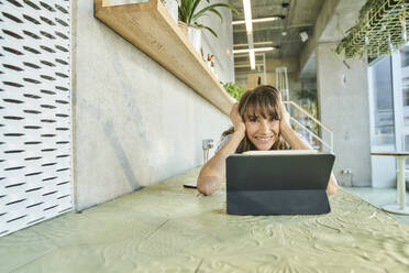 Smiling woman with head in hands using digital tablet while lying on table at home - FMKF06623