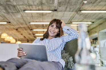 Smiling woman using digital tablet while sitting at home - FMKF06626
