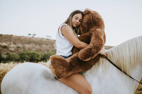 Portrait of beautiful young woman embracing large teddy bear while sitting on horseback with closed eyes - MIMFF00249