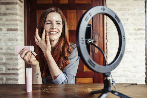 Smiling woman applying cream while filming make up tutorial on mobile phone at home - JSMF01821