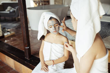 Mother in towel applying facial cream on daughter face while sitting at home - JSMF01872