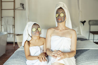 Mother and daughter in towel with facial mask and slice of cucumber on eyes sitting at home - JSMF01875