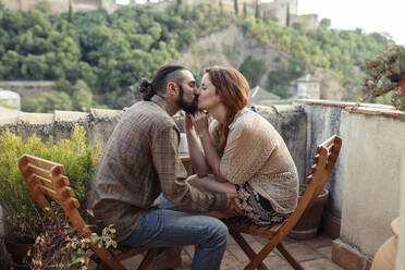 Couple kissing while sitting on chair at rooftop - JSMF01881