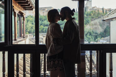 Couple kissing while standing by window at home - JSMF01887