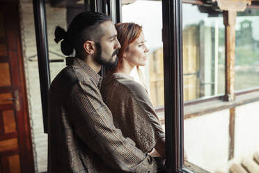 Man and woman standing by window at home - JSMF01890