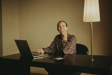 Smiling female entrepreneur looking away while working on laptop in office - DMGF00186