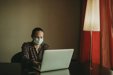 Businesswoman wearing protective face mask working on laptop in office - DMGF00192