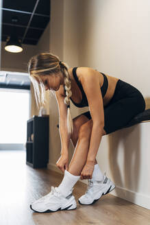 Young sportswoman pulling sock sitting on counter in gym - MPPF01165