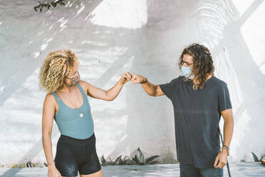 Couple with face mask giving fist bump while standing against wall - DAMF00549