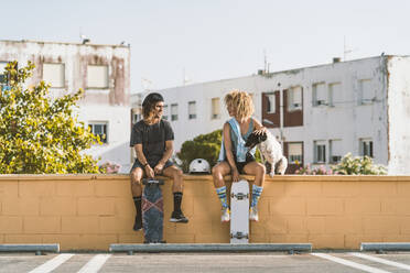 Friends with skateboard and dog talking while sitting on retaining wall in city - DAMF00555