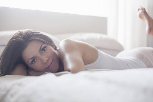 Young woman lying down on bed in bedroom at home - AJOF00239