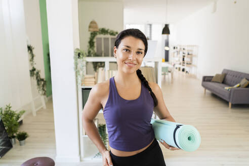 Young woman with hand on hip with exercise mat standing at home - GIOF09165