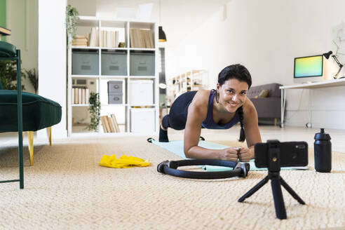 Young fitness woman video recording on camera while doing push ups at home - GIOF09177