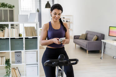 Smiling young woman using smart phone while sitting on exercise bike at home - GIOF09189