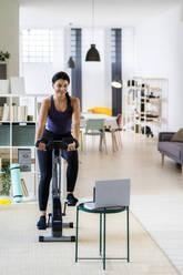 Female athlete exercising on exercise bike while using laptop at home - GIOF09192