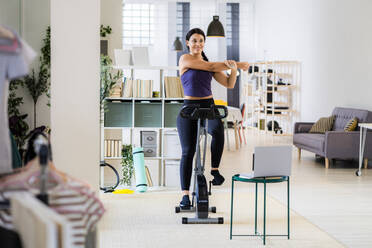 Young female athlete smiling while doing stretching exercise sitting on exercise bike at home - GIOF09195