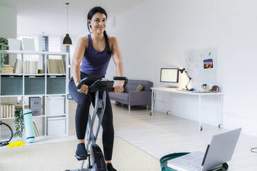 Smiling young woman listening music through bluetooth while sitting on exercise bike at home - GIOF09198
