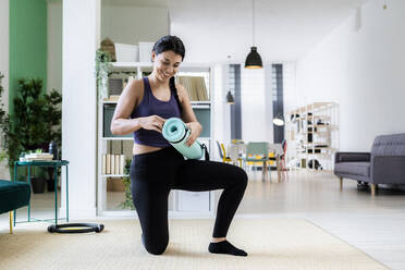 Young woman holding exercise mat while kneeling at home - GIOF09201