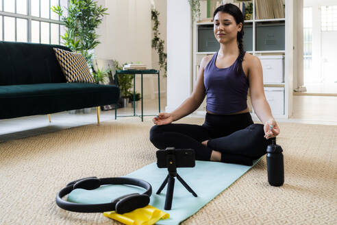 Female athlete meditating while video recording on camera at home - GIOF09210