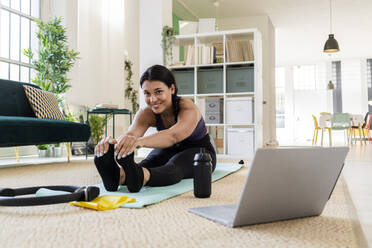 Smiling female athlete doing stretching exercise while sitting at home - GIOF09213