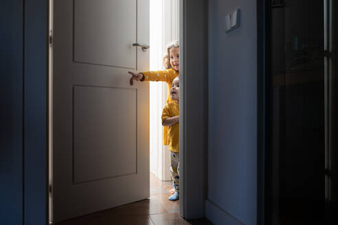 Charming brother and sister peeping out from door in modern apartment while having fun and looking away - ADSF16657