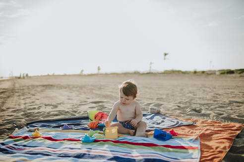 Male toddler playing with toys at beach during sunset - GMLF00726