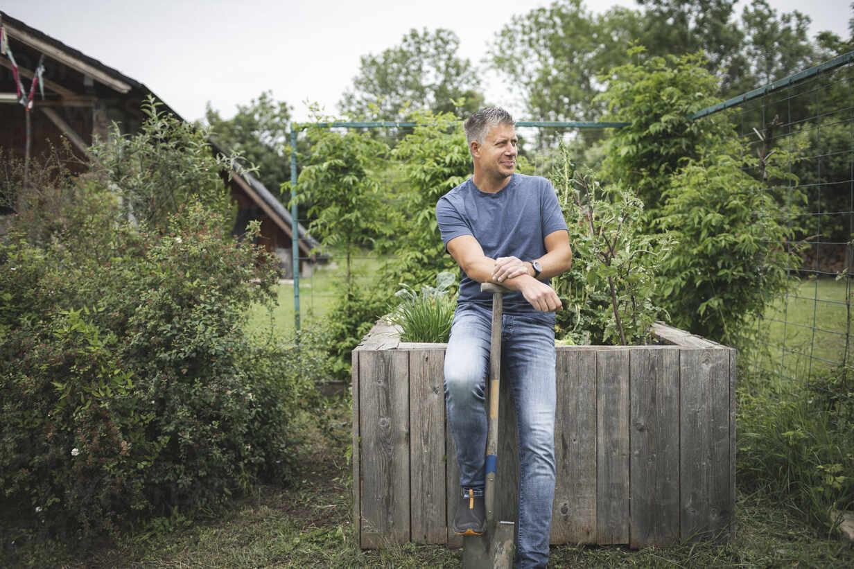 Lächelnder hübscher Mann hält Spaten und schaut weg, während er sich auf ein hölzernes Hochbeet im Gemüsegarten stützt - HMEF01078 - Epiximages/Westend61