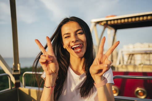 Smiling beautiful woman showing peace sign while enjoying Ferris wheel ride - OYF00215