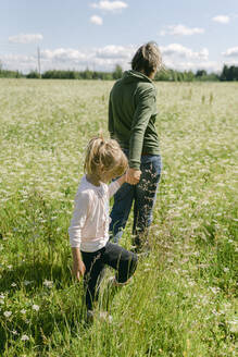 Mother holding hand of daughter while walking on meadow - PSIF00397