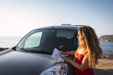 Woman looking at map while standing by camper van at beach - DCRF00958