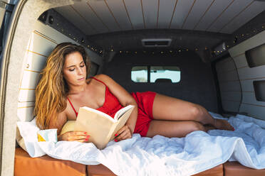 Woman reading book while lying in camper van at beach - DCRF00973