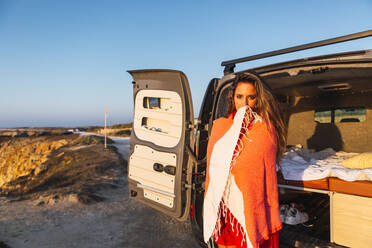 Young woman covered in shawl standing by camper van at beach - DCRF00982
