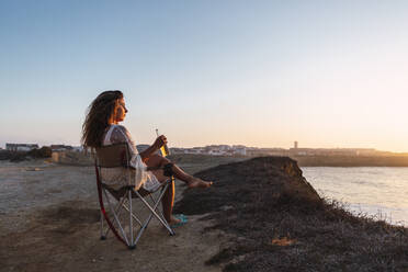 Woman drinking white wine while sitting on chair at beach during sunset - DCRF00991