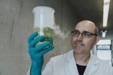 Scientist holding liquid flask with evaporating smoke while standing at clinic corridor - MFF06304