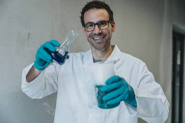 Smiling man holding liquid solution beaker while standing at clinic corridor - MFF06307