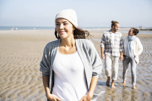 Smiling woman looking away while walking with boyfriend and mother in background at beach - UUF21667